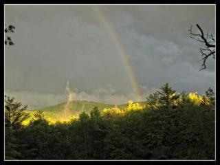 Rainbow on dark sky with patches of sun on ground in foreground