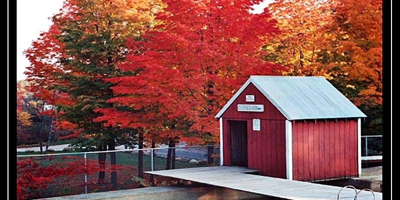 Small building at Mill Pond - in background are trees in Autum colors